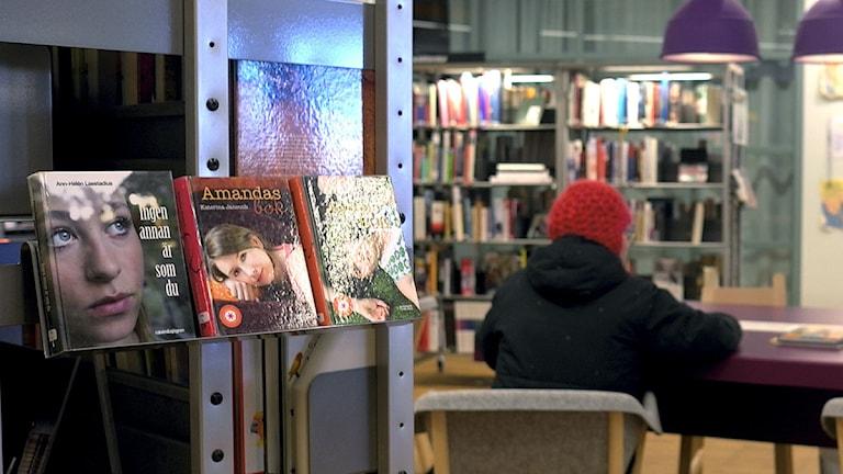 Kvinna sitter och läser på bibliotek. Foto: Hasse Holmberg/Scanpix