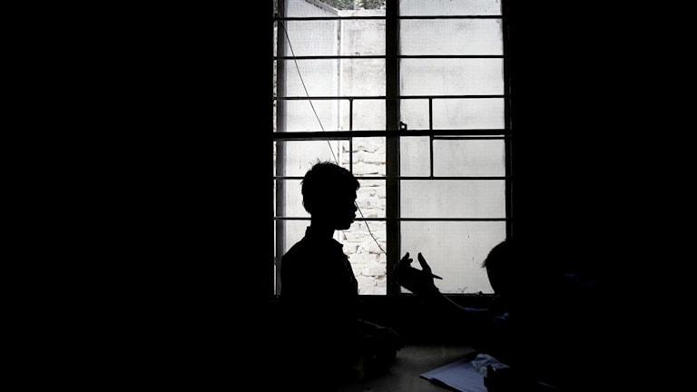Silhuetten av ett barn och en person som sitter ner i ett mörkt rum vid ett fönster. Foto: Scanpix.