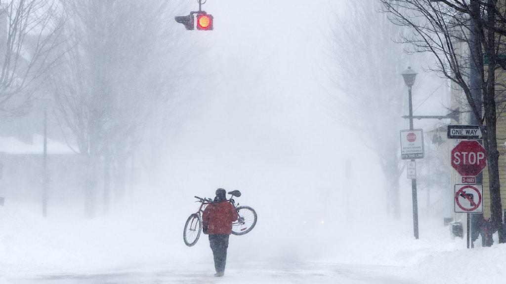 En man bär sin cykel längs en gata med snörök i Portland i Maine, USA. Foto: Robert F. Bukaty/Scanpix.