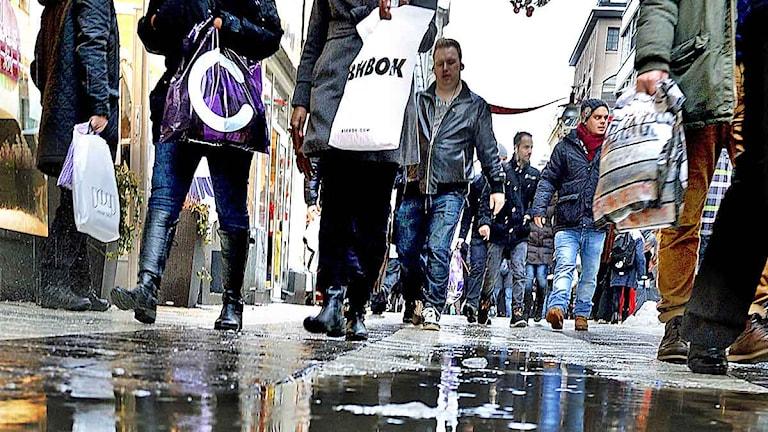 Flera personer med plastkassar från olika butiker går nerför Drottninggatan i Stockholm. Foto: Tomas Oneborg/Scanpix.