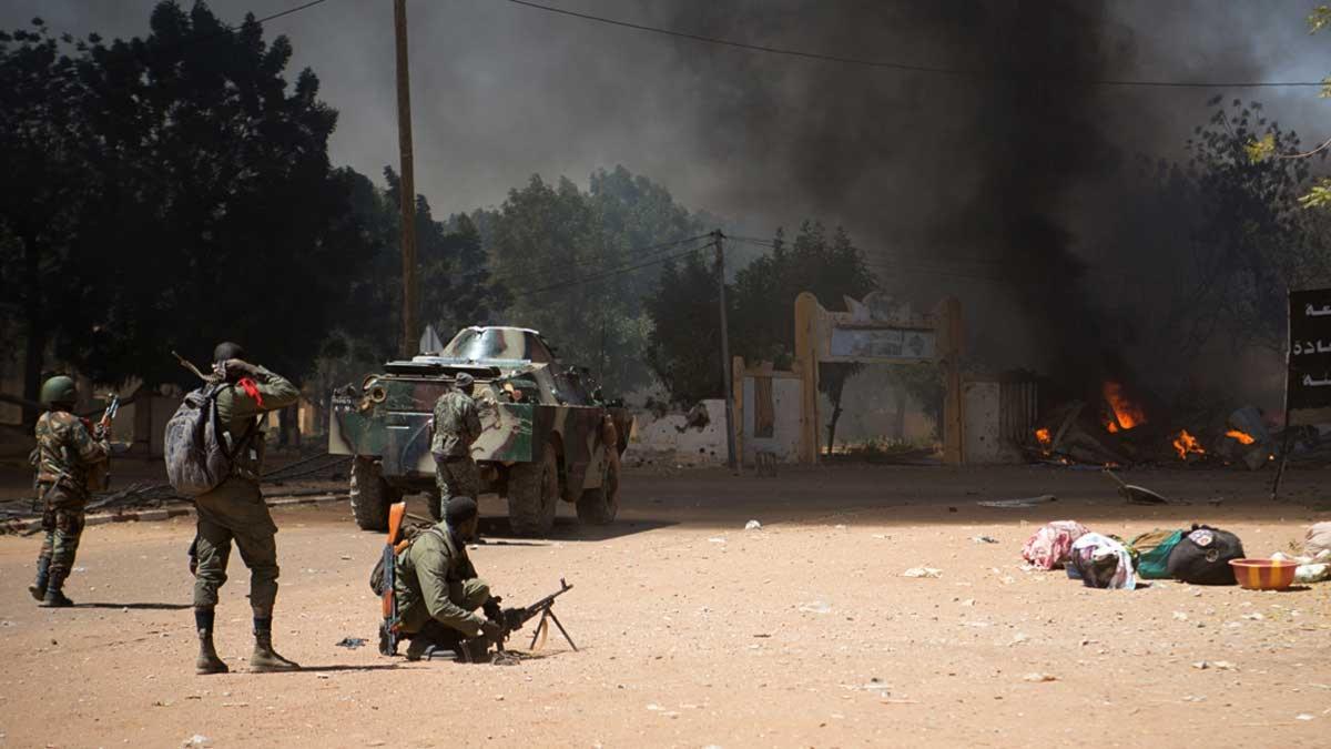 Soldater och en stridsvagn framför en brinnande byggnad.