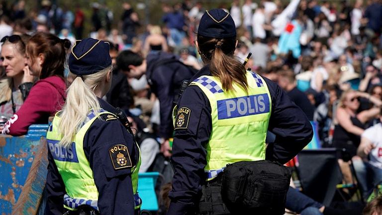 Man ser ryggen på två kvinnliga poliser som blickar ut över ett folkhav.