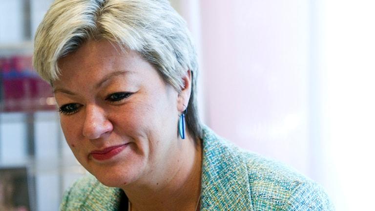 Ylva Johansson är socialdemokrat. Hon bär blågrön kaval på bilden och ett blått örhänge. Hon har kortklippt ljust hår.