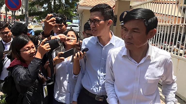 De två spionanklagade journalisterna pratar med journalister utanför domstolen.
