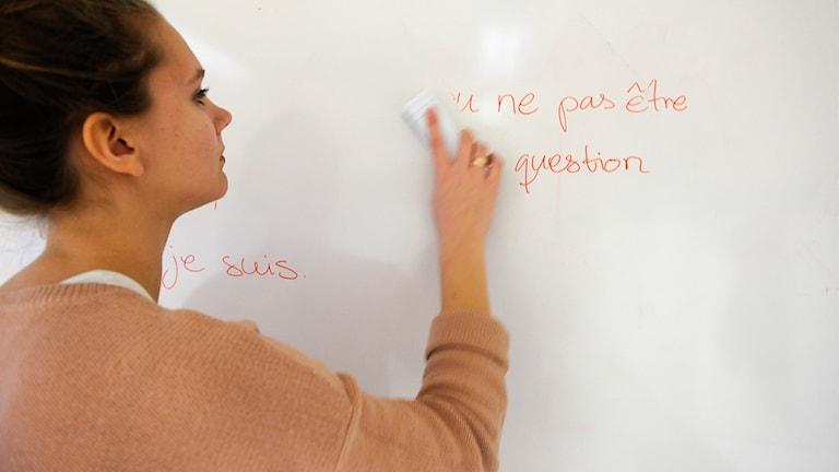 Kvinna framför klassrumstavla