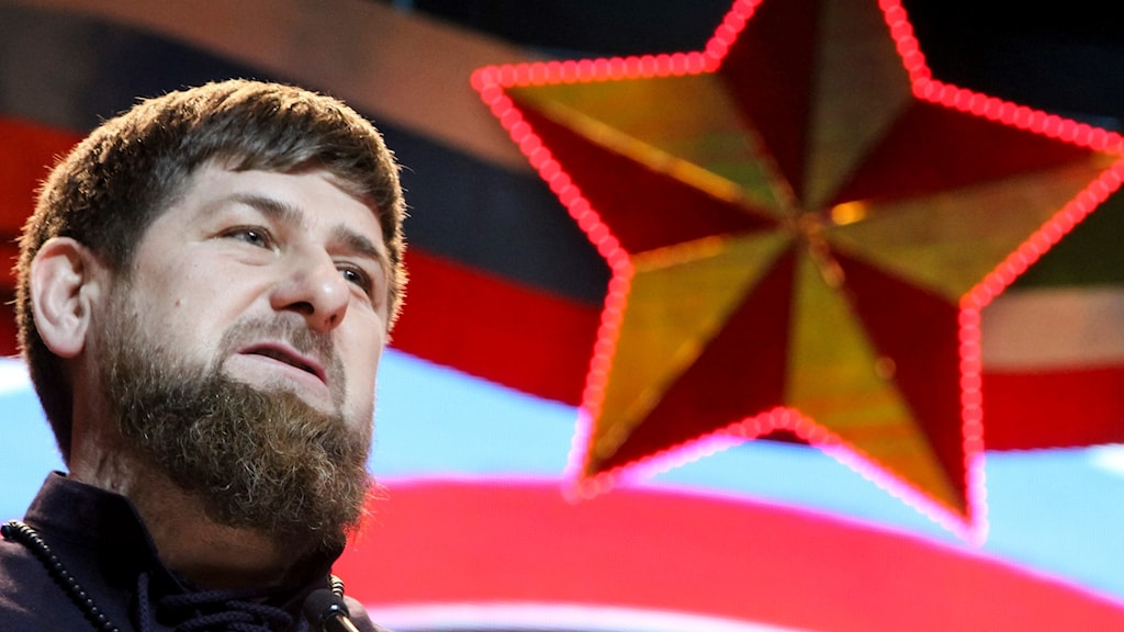 En man står framför avbildning av en röd stjärna.