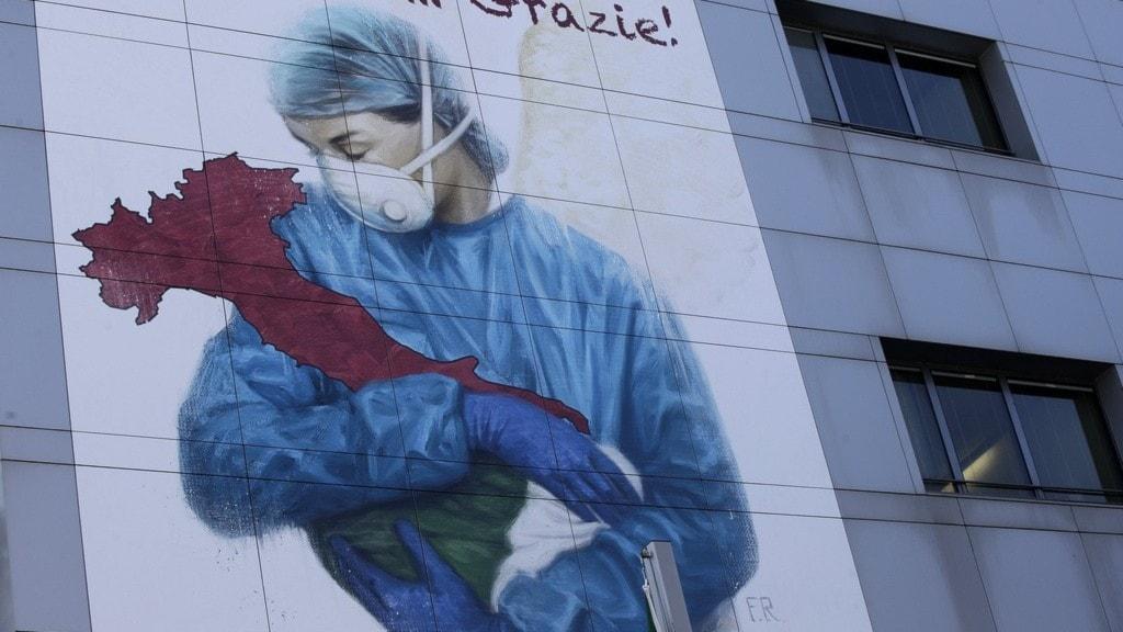 En väggmålning med en sjukvårdspersonal med munskydd.