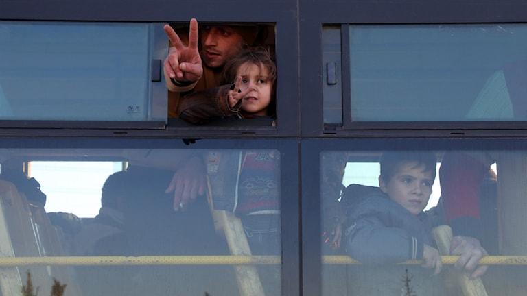 Två syrier gör fredstecknet efter att ha ankommit till rebellkontrollerade Khan al-Aassal-regionen.