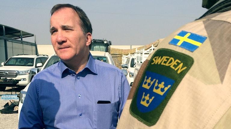 Man i blå skjorta och en person i militärkläder med ett svenskt märke och flagga  i förgrunden.