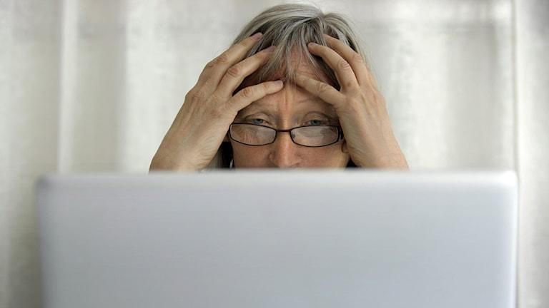 Teknikstrul. En fundersam medelålders kvinna sitter framför en dator som inte fungerar. Foto: Janerik Henriksson/Scanpix