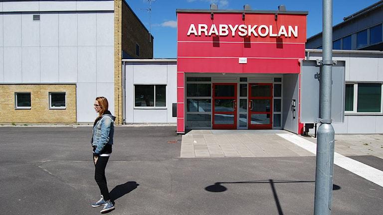 Elev står på gården framför Arabyskolans entré. Foto: Marcus Eriksson/Sveriges Radio.