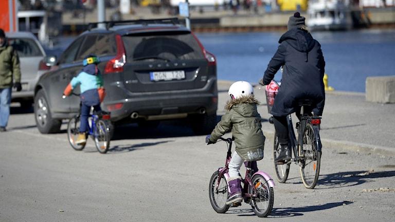 Två små cyklister med hjälm och en vuxen utan hjälm i solen vid Skeppsholmen i centrala Stockholm. Foto: Janerik Henriksson/Scanpix.
