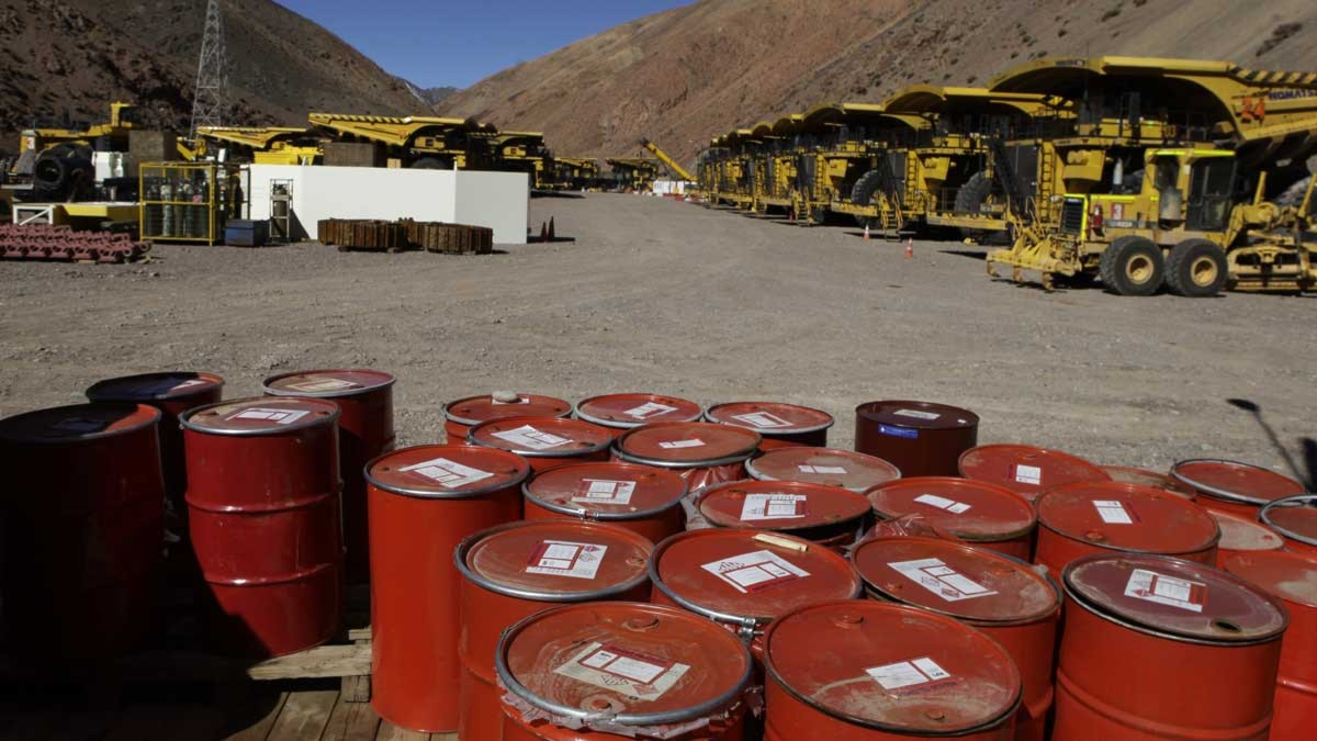 Röda tunnor står på en grusplan vid massor av gula lastbilar. Vid pascua lama-gruvan i Chile.