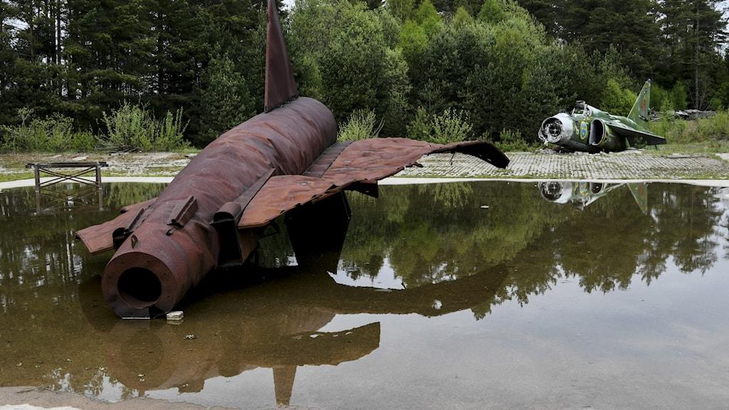 Rostrött gammalt Viggenplan i en vattenpöl.