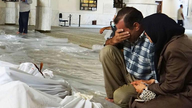 En man och en kvinna sitter och sörjer vid en död kropp efter den misstänkta gasattacken i Syrien. Foto: TT.