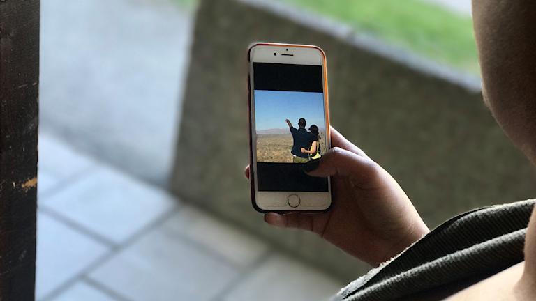 En kvinna visar en bild på sin mobiltelefon. Bilden föreställer henne och hennes man sett bakifrån.