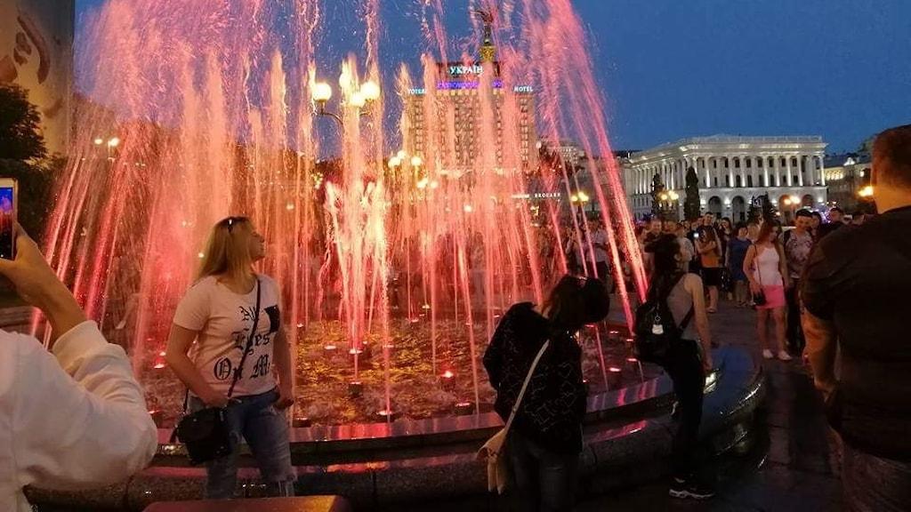 Postkassörskan Veronika fotograferas framför en av Majdans fontäner