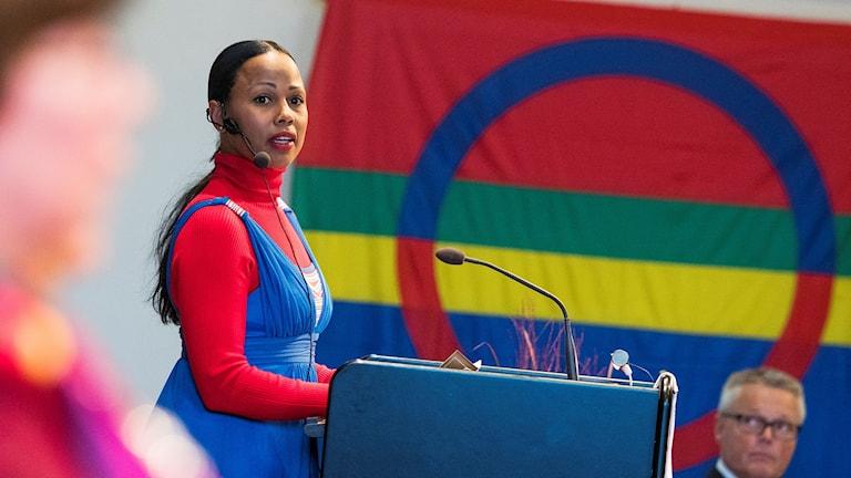 Alice Bah Kuhnke står vid en mikrofon framför den samiska flaggan.