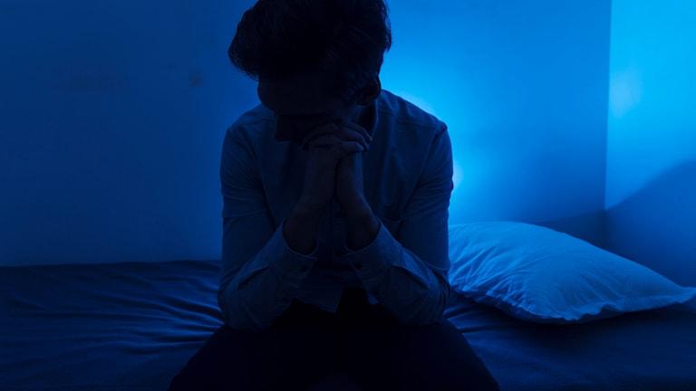 Person som sitter på sängen i ett mörkt rum