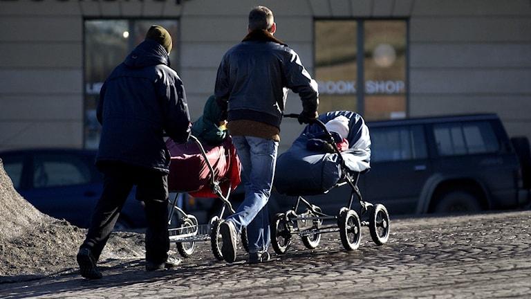 Två pappor på barnvagnspromenad.
