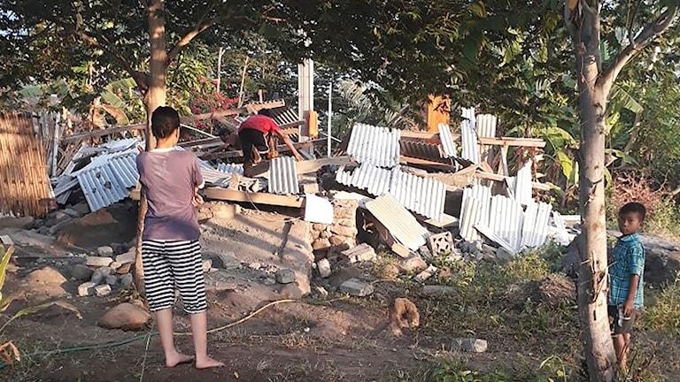 Personer tittar på sina förstörda hus i Lombok.