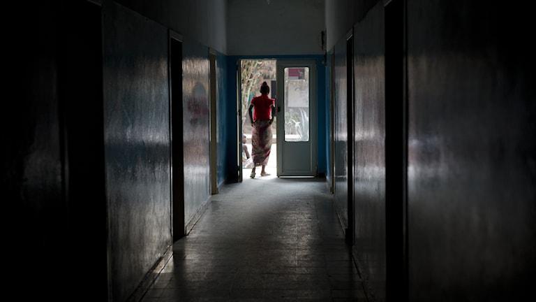 Afrikansk kvinna går ut från en mörk sjukhuskorridor mot ljuset.