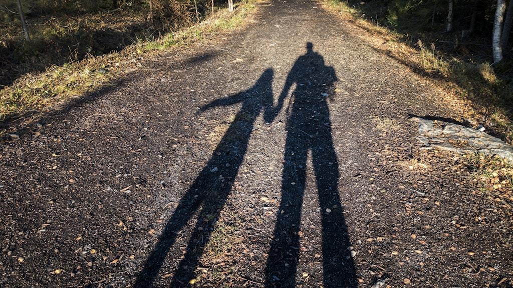 Skuggor på en väg av en vuxen och ett barn