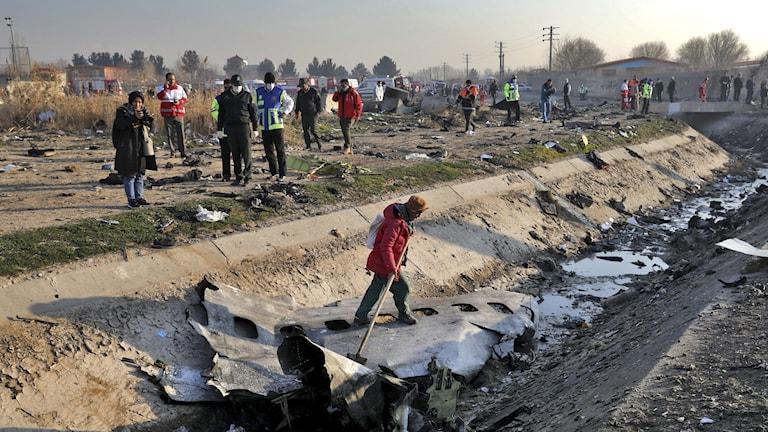 Räddningsarbetare vid platsen där planet kraschade.