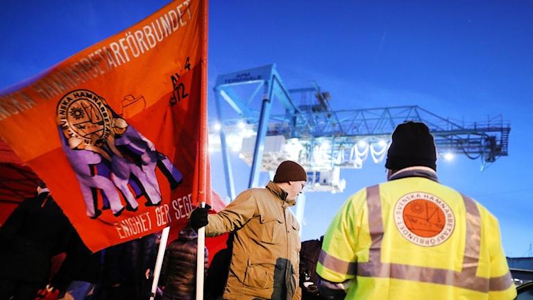 Man håller i röd flagga med texten Hamnarbetarförbundet, en hamnkran i bakgrunden.