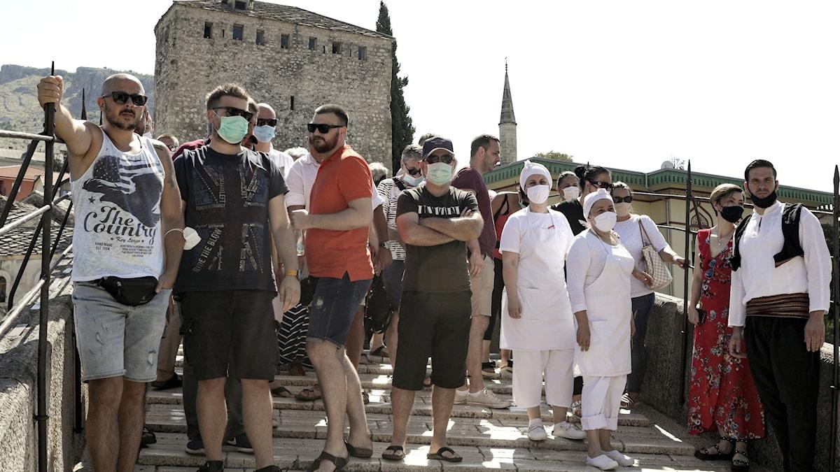 Personer med munskydd på bro.