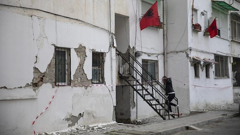 Kvinna går in i ett jordbävningsskadat hus.
