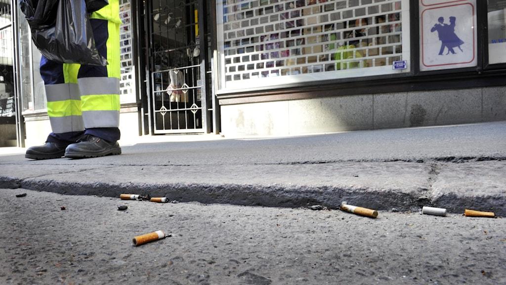 En man i varselkläder plockar skräp. Många fimpar ligger på marken.