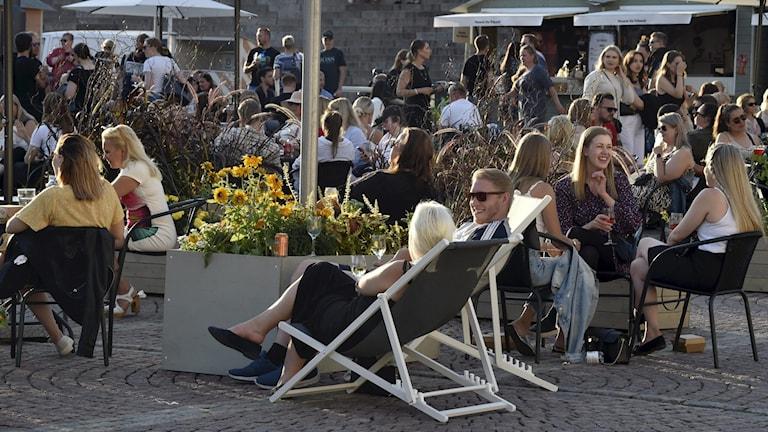 Människor på en uteservering på Senatstorget i Helsingfors.