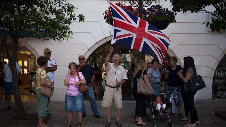 En man höjer den brittiska flaggan i Gibraltar på Casesmates torg.