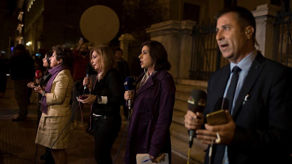 Grekiska jpurnalister står utanför domstolsbyggnaden i centrala Aten och rapporterar.