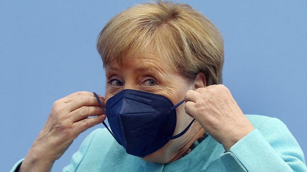Korthårig kvinna som tar på sig svart ansiktsmask