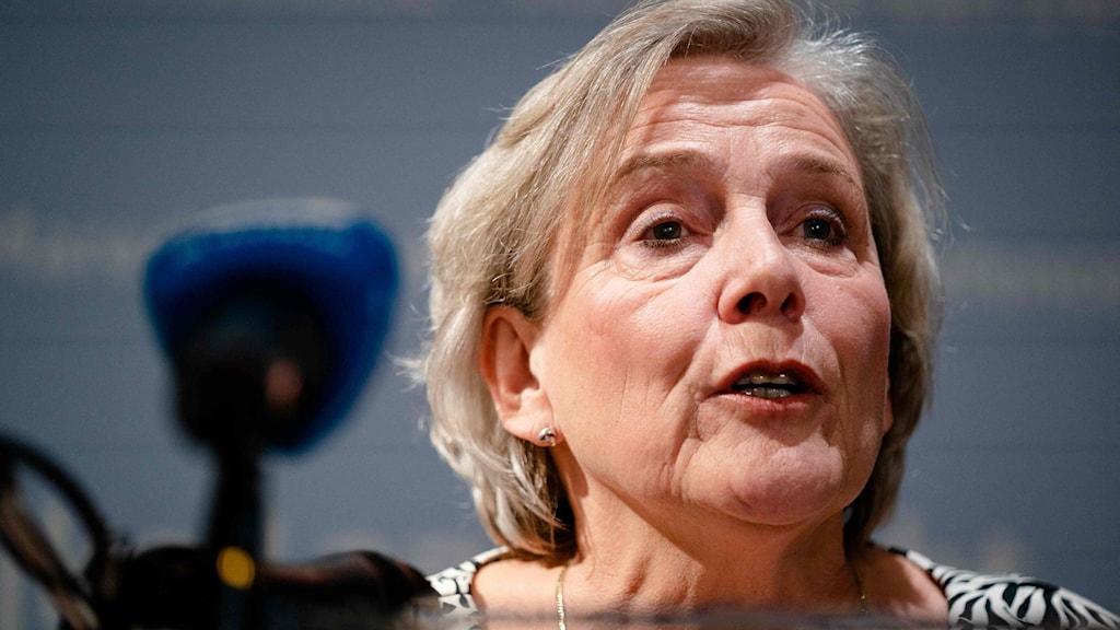 Korthårig blond äldre kvinna säger något bakom en mikrofon