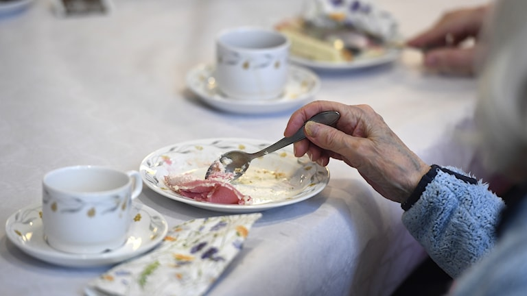 Kvinna äter tårta på ett äldreboende.