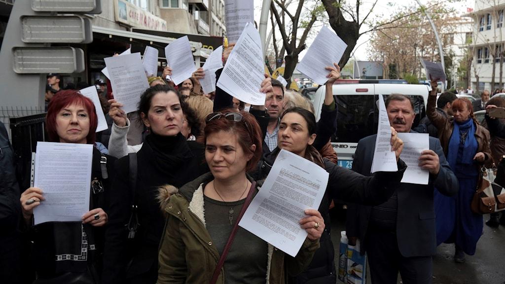 Flera människor med papper i handen.