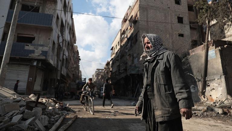 En man tittar på stenar från ett förstört hus.