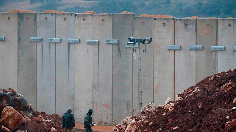 Israeliska soldater står intill betongmuren längs gränsen mot Libanon.