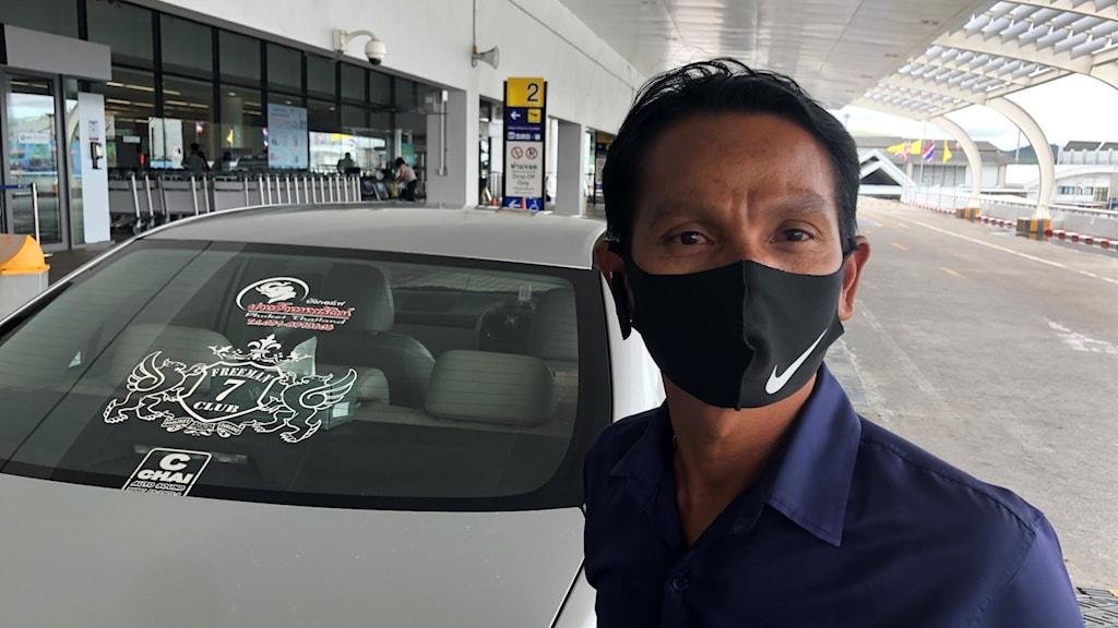 Man med munskydd framför en taxibil i Thailand.