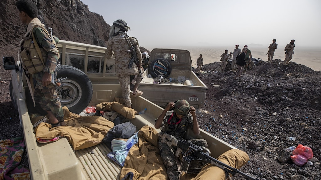Tre män på en lastbil under kriget i Jemen.