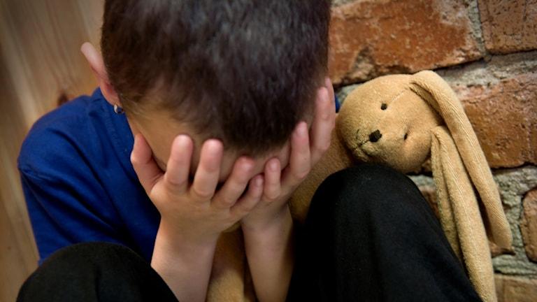 Pojke sitter och gråter och kramar sitt gosedjur.