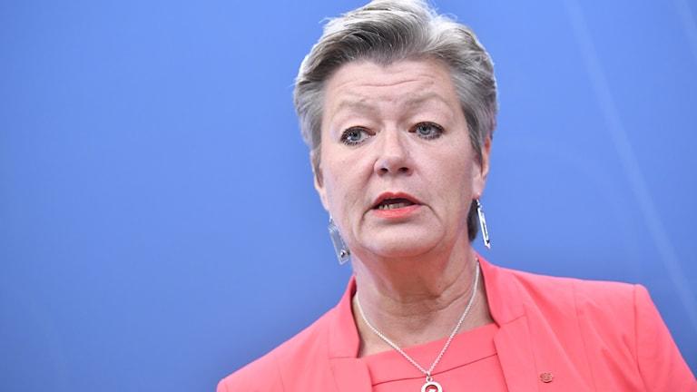 Ylva Johansson i röd kavaj mot blå bakgrund.