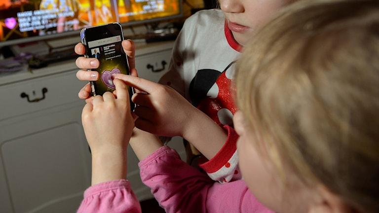 Barn visar Mello-appen som används vid röstning under Melodifestivalen.