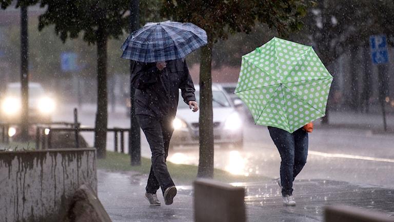 Två personer med paraply i regnet.