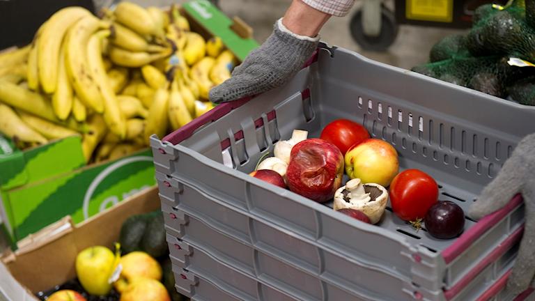 Gamla grönsaker i en plastback i butik