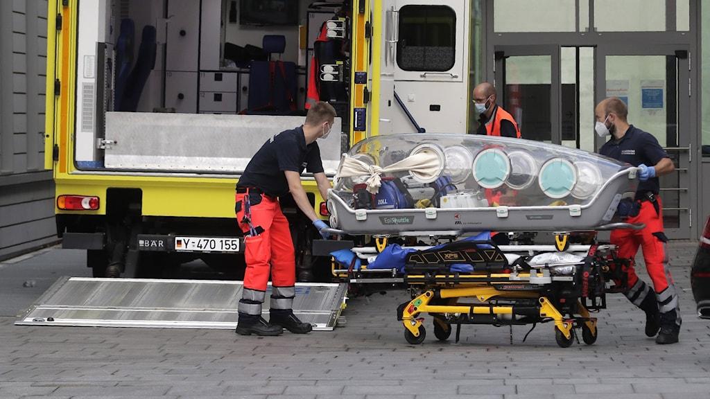 Två sjukvårdare med person på bår.