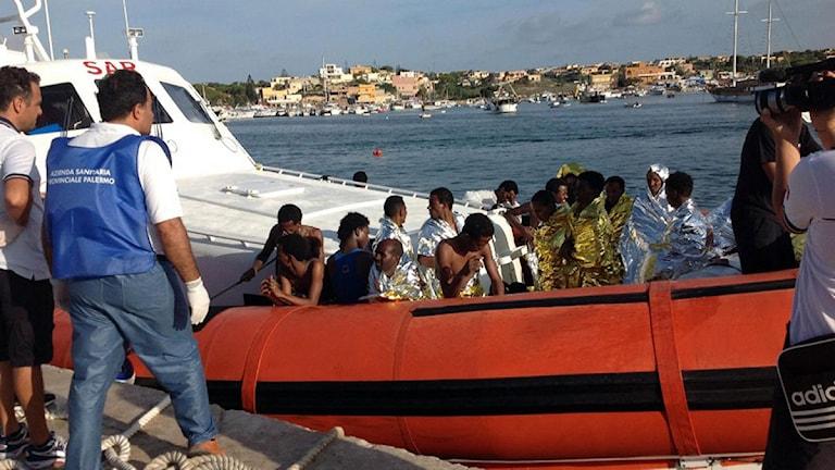 Italienska kustbevakningen för in migranter som räddats i Lampedusas hamn. Foto: Nino Randazzo/AP/TT.